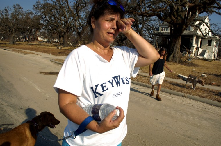September 2, 2005 - Angelique Lanier breaks into tears as she and her boyfriend, Luther Broadus, walk along Highway 90 in Biloxi and the homes destroyed there. They were walking their own dog and one they rescued (left). Broadus had tried to rescue the dog during the storm as it floated by their home but could not. They found it again on Tuesday and have been caring for it since.  (Christopher T. Assaf/Baltimore Sun)