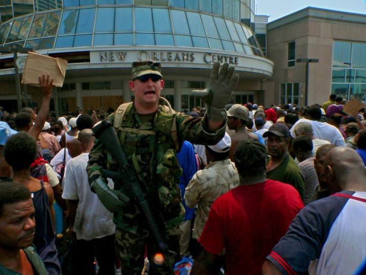 August 2, 2005 - A member of the National Guard implores hurricane survivors to step back, claiming that young and old were being pressed against the door of the New Orleans Shopping Center. in the aftermath of Hurricane Katrina in New Orleans, LA. Buses rolled in and out, taking up to 50 people per bus to help evacuate the Superdome, which had become uninhabitable. (Karl Merton Ferron/Baltimore Sun)