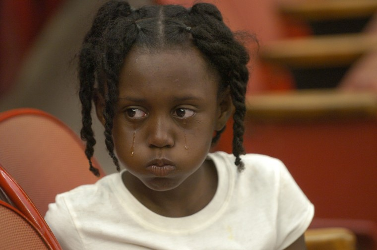 September 2, 2005 - Derinque Sylvester, 7, who was evacuated with her grandmother Sheliah Lyons and other family members by helicopter from the roof of their two-story apartment building on Thursday morning after they were trapped by the floods, cries after a brief argument with her cousin while sitting with other evacuees from Hurricane Katrina at the Houston Astrodome. (John Makely/Baltimore Sun)