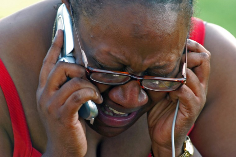 September 2, 2005 - With her cell phone charged after being plugged into a gasoline- powered generator, DeShawn Handy Henderson weeps as she finally contacts relatives in Houston after days without being able to reach them while standing on an on-ramp to Interstate 10 in the aftermath of Hurricane Katrina in New Orleans, LA. (Karl Merton Ferron/Baltimore Sun)