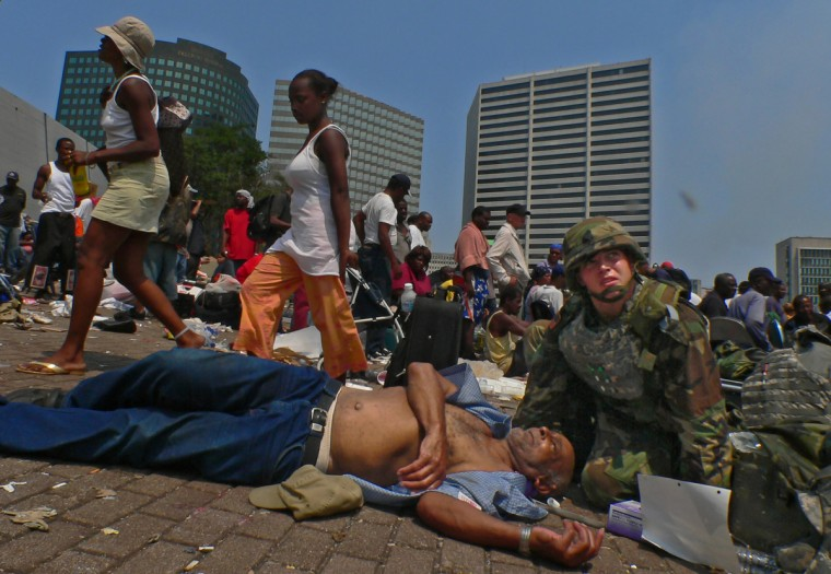 September 2, 2005 --Other hurricane survivors walk past as a member of the National Guard tries to comfort an elderly man who collapsed in the heat while waiting for his turn to be evacuated in New Orleans, LA. (Karl Merton Ferron/Baltimore Sun)