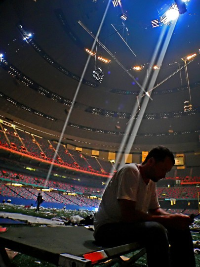 September 2, 2005 - Light streams through from holes in the evacuated Superdome stadium, with litter strewn all over the field as Eddie Peterman of the Garden District sits, opening a packet from a MRE (meals ready to eat) in the aftermath of Hurricane Katrina in New Orleans, LA. (Karl Merton Ferron/Baltimore Sun)