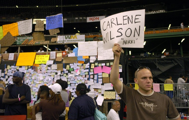 September 2, 2005  - Houstonian Adam Lesage holds up a sign trying to locate his best friend's, friend's sister who was evacuated to the Astrodome. (John Makely/Baltimore Sun)