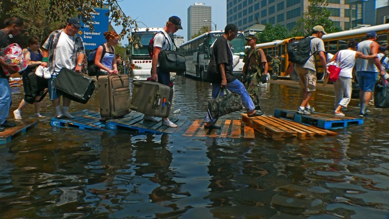 September 2, 2005 - Survivors step on wooden pallets as they cross through standing water on their way to waiting buses that carried them away from Mid City.  Buses rolled in and out, taking up to 50 people per bus to help evacuate the Superdome, which had become uninhabitable. (Karl Merton Ferron/Baltimore Sun)