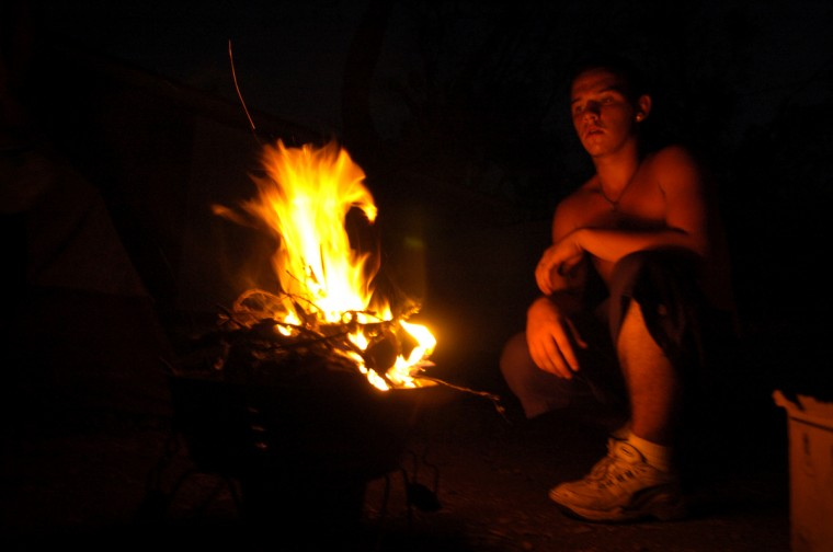 September 4, 2015 - Jason Fowler, 18, lights a fire as it gets dark in Gulfport, Ms. He and his family have been camping next to their damaged trailer, without power and water, since Hurricane Katrina hit the Gulf Coast a week before. The Fowler family's trailer was flooded by the surge of Hurricane Katrina and the roof was damaged by a fallen tree making it impossible for them to live inside. (Christopher T. Assaf/Baltimore Sun)
