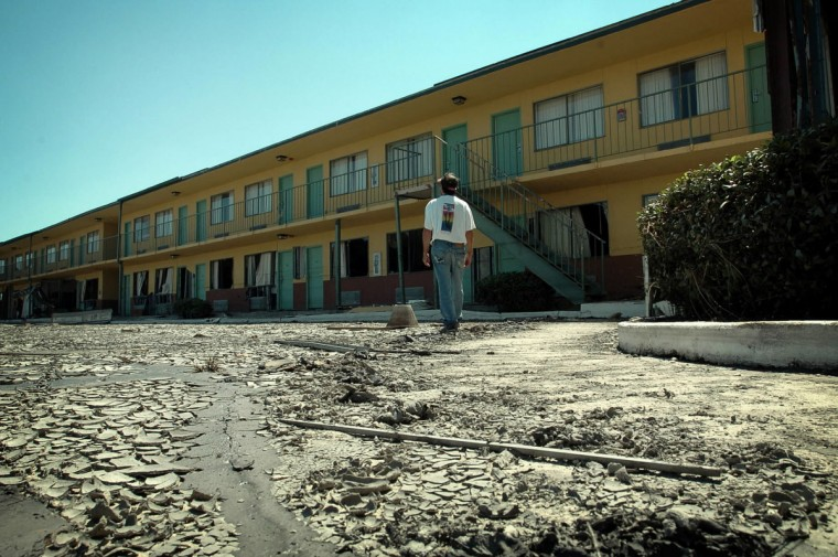 September 7, 2005 - After the water receded, dried, caked mud remained as evidence. Ralph Simmons walks around the back of the Econo Lodge Chalmette in St. Bernard's Parish. Simmons, 49, and Jose Bolanos, 55, have been living at the motel since Hurricane Katrina swamped this coastal community. They lived off whatever they could salvage, sometimes scavenging food and bottled water from the diesel and oil polluted water surrounding them.  (September 7, 2005 - Ralph Simmons stands in the downstairs rubble of the hotel he used to work in Chalmette, LA.  He has been living at the Econo Lodge Chalmette in St. Bernard's Parish, since Hurricane Katrina swamped this coastal community. He has worked at the hotel for six years and moved in after his house was destroyed.  (André F. Chung/Baltimore Sun)/Baltimore Sun)