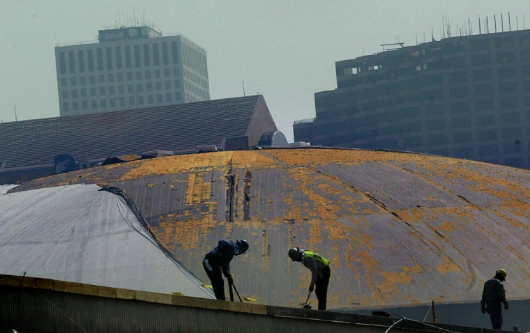 September 19, 2005 - A couple of roofers work to make repairs to an industrial building with the Superdome behind them as the city of New Orleans begins to let business and people trickle back into the area after Hurricane Katrina. (Monica Lopossay/Baltimore Sun)