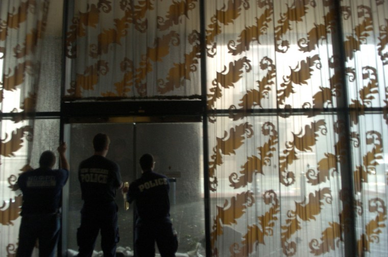 August 29, 2005 -  New Orleans Police officers watch  Hurricane Katrina blow through New Orleans from the safety of The J.W. Marriott hotel. (John Makely/Baltimore Sun)