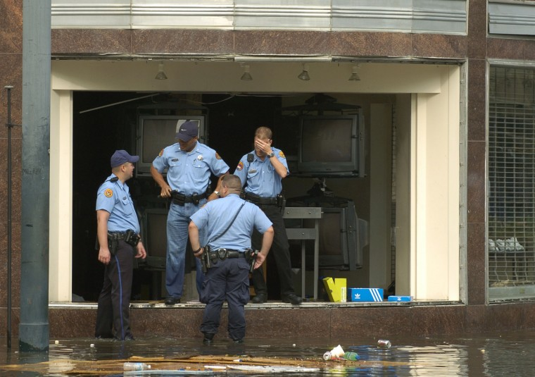 August 30, 2005 -  New Orleans police chased looters from a clothing store with armloads of items after the floodwaters that began rising after Hurrican Katrina came through town. (John Makely/Baltimore Sun)