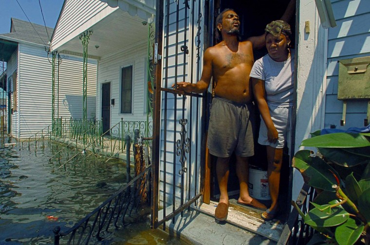 September 4, 2005 - Pamela Wynn and Glenn Mack look out from the front entrance of their home in the eastern New Orleans, six days after Hurricane Katrina devastated much of the gulf coast. Some residents had decided to remain, even as they were surrounded by flooding and had the option to evacuate. (Karl Merton Ferron/Baltimore Sun)