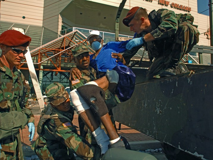 September 8, 2005 - Military personnel work together to help offload Milton Smith (in blue) from a personnel carrier outside the Convention Center to move him to be airlifted after he and other residents were rescued from the ninth floor of a nursing home as the mandatory evacuation was initiated throughout New Orleans. (Karl Merton Ferron/Baltimore Sun)