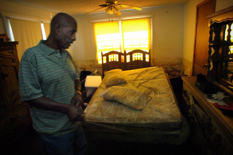 September 11, 2005 - Sidney Bibbins, 64, checks on his house. Water came into the first floor and ruined everything, floating the mattress in the guest bedroom. (André F. Chung/Baltimore Sun)