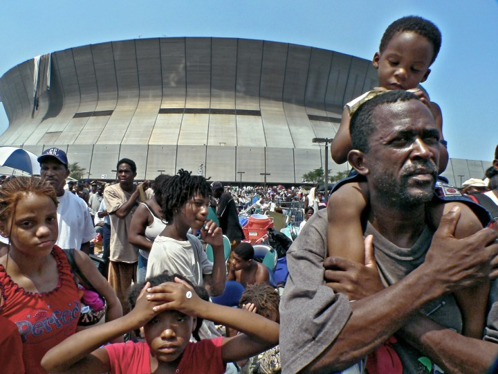 September 2, 2005 - Bruce Merritt, Jr., 3 sits atop his father Bruce Merritt, as Angela Spear, 9 and Spear, 13 (left) look on while Bruce Sr., his wife and 8 children wait for word to leave. in the aftermath of Hurricane Katrina in New Orleans, LA. (Karl Merton Ferron/Baltimore Sun)