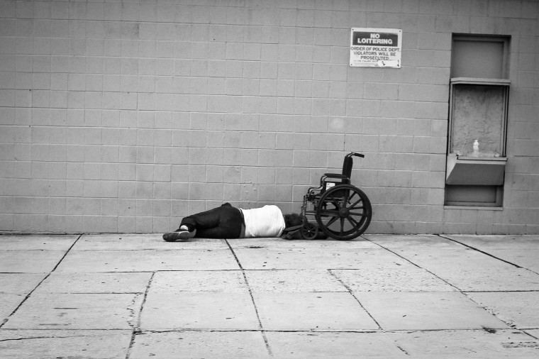 man laying next to wheelchair