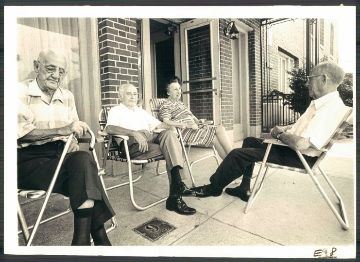 Four residents sit outside the once-elegant Temple Gardens apartments in Reservoir Hill on Aug. 13, 1973. (Baltimore Sun photo by Weyman Swagger)