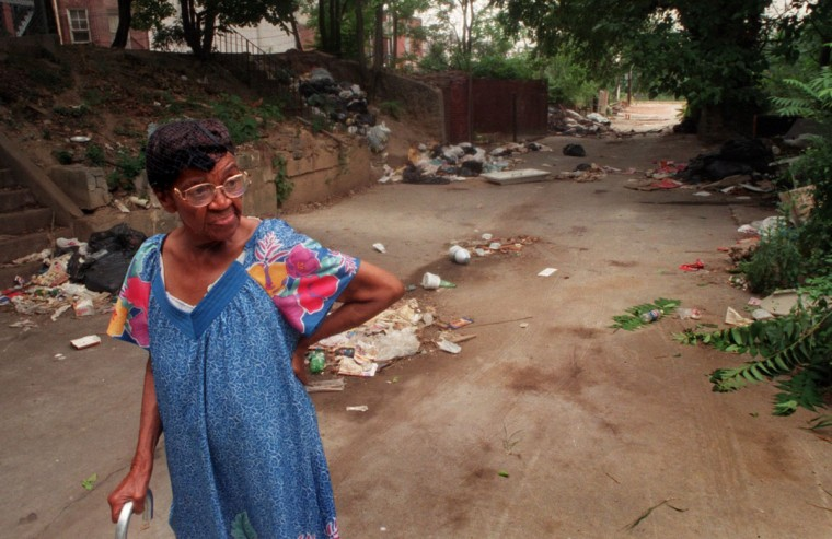 Piles of trash are strewn across Mason Alley, between Whitelock and Ducatel Streets in Reservoir Hill, making the alley unfit for residents and an obstacle course for drivers. Martha Franks, 83, whose backyard faces the alley, is pictured July 21, 1999. (Amy Davis / Baltimore Sun)