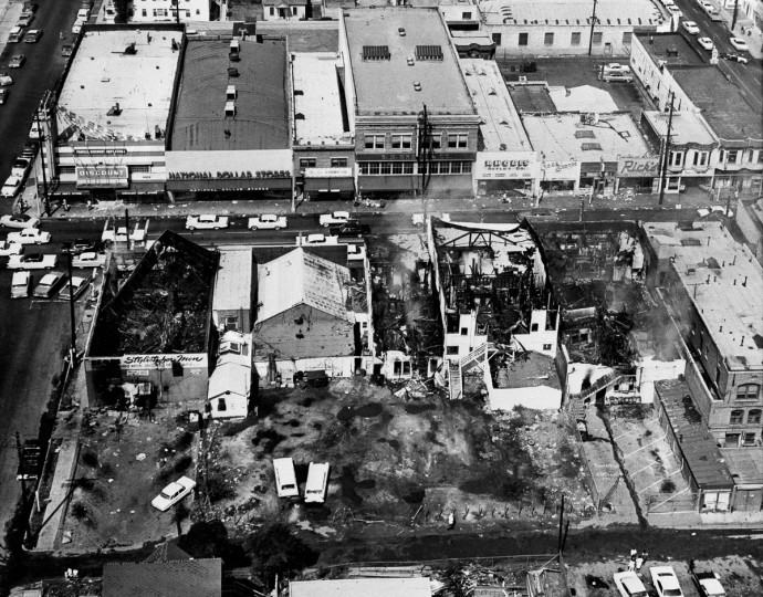 This Aug. 14, 1965 file photo shows several burned-out structures after fires started by fires started rioters destroyed a business block in the Watts district of Los Angeles. It began with a routine traffic stop 50 years ago this month, blossomed into a protest with the help of a rumor and escalated into the deadliest and most destructive riot Los Angeles had seen. The Watts riot broke out Aug. 11, 1965 and raged for most of a week. When the smoke cleared, 34 people were dead, more than a 1,000 were injured and some 600 buildings were damaged. (AP Photo, File)