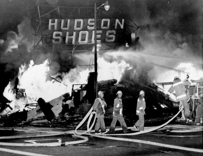 In this Aug. 14, 1965 file photo, firefighters battle a blaze set in a shoe store that collapses in flames during rioting in the Watts district of Los Angeles. It began with a routine traffic stop 50 years ago this month, blossomed into a protest with the help of a rumor and escalated into the deadliest and most destructive riot Los Angeles had seen. The Watts riot broke out Aug. 11, 1965 and raged for most of a week. When the smoke cleared, 34 people were dead, more than a 1,000 were injured and some 600 buildings were damaged.(AP Photo, File)