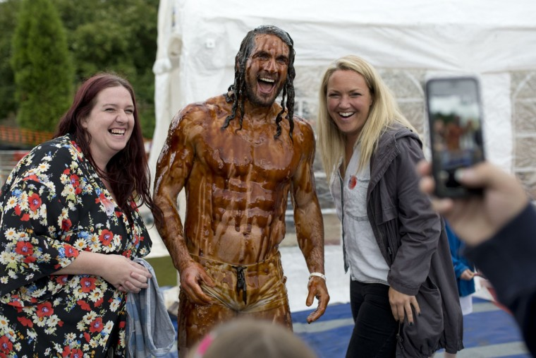 Joel Hicks poses for a photograph with supporters after winning the men's title in the 8th annual World Gravy Wrestling Championships at the Rose n Bowl Pub in Bacup, north west England on August 31, 2015. (OLI SCARFF/AFP/Getty Images)
