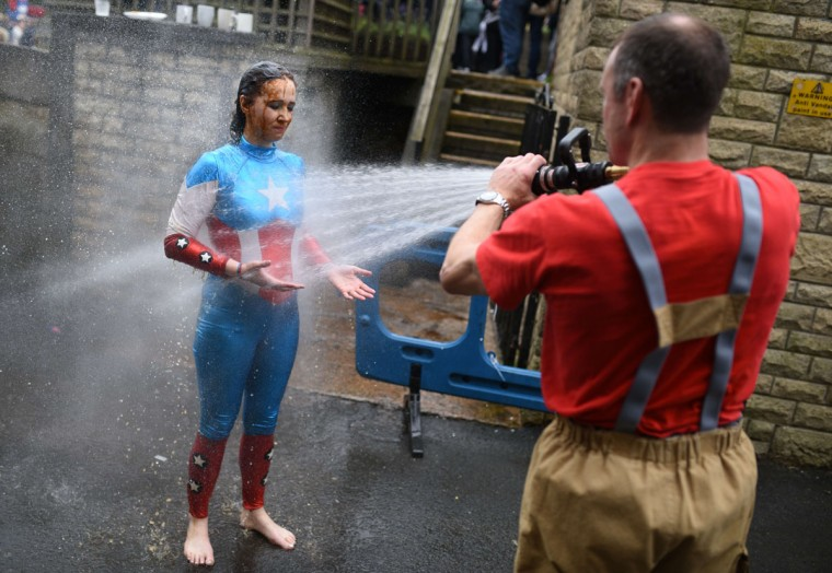 A competitor is hosed-down by the fire brigade after taking part in the 8th annual World Gravy Wrestling Championships at the Rose n Bowl Pub in Bacup, north west England on August 31, 2015. (OLI SCARFF/AFP/Getty Images)