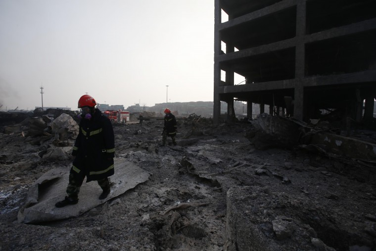 Firefighters walk past a damaged building at the site of the explosions in Tianjin on August 15, 2015. Residents near the site of two giant explosions in the northern Chinese port city of Tianjin were being evacuated on August over fears of toxic contamination, state media said. AFP/Getty Images