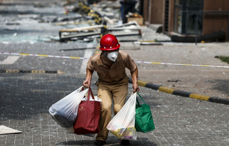 A victim of the explosions carrying his belongings walks out of his home in a residential area near the site of the explosions in Tianjin on August 15, 2015.  Residents near the site of two giant explosions in the northern Chinese port city of Tianjin were being evacuated on August 15 over fears of toxic contamination, the official Xinhua news agency said. AFP/Getty Images
