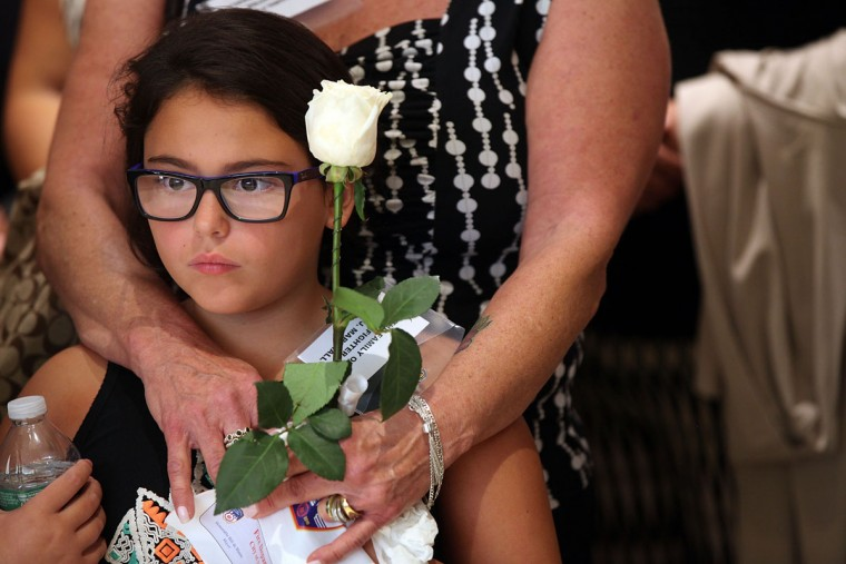Annalise Marshall (8), whose grandfather firefighter James T. Marshall died of illnesses related to his work at the World Trade Center, attends a ceremony at the Fire Department of New York headquarters where names were added to a memorial wall for deaths related to World Trade Center illnesses on September 8, 2015 in New York City. A total of 21 names were added to the memorial which was unveiled in September 2011 and already lists the names of 89 FDNY members who died of illnesses related to their work at the World Trade Center site during and after the 9/11 attacks. (Photo by Spencer Platt/Getty Images)