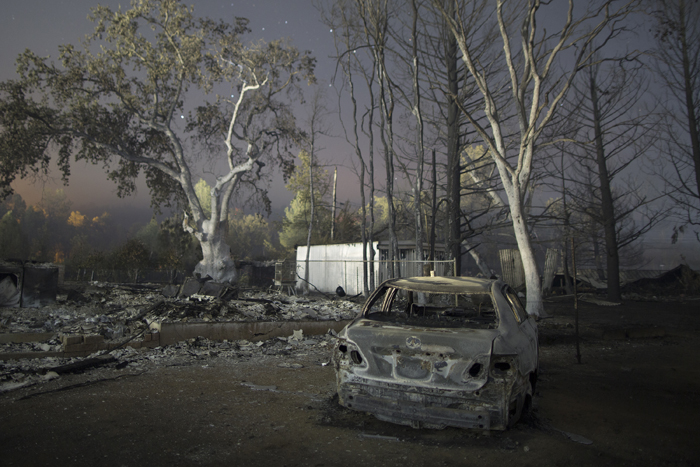 A charred car stands with the ruins of a home that burned in the Valley Fire are seen on Tuesday in Middletown, California. The 104-square-mile fire was 15 percent contained and has destroyed 585 homes and hundreds of other structures.  (David McNew/Getty Images)