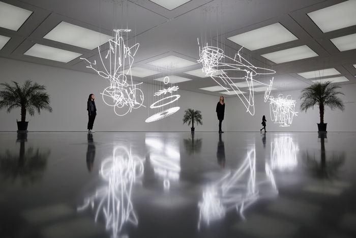 "Gallery staff and visitors walk around pieces of work entitled ""Neon Forms (after Noh I,II and II)"" by Welsh Artist Cerith Wyn Evans during a press preview at the White Cube Gallery in Bermondsey on Tuesday in London. The works consisting of suspended neon lights filled with illuminating gas will be shown at the gallery until Nov. 15.(Dan Kitwood/Getty Images)"