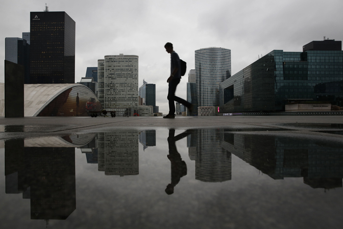 A man is reflected in a rain puddle as he walks through the business district of La Defense, west of Paris, on Tuesday. (FLORIAN DAVID/AFP/Getty Images)