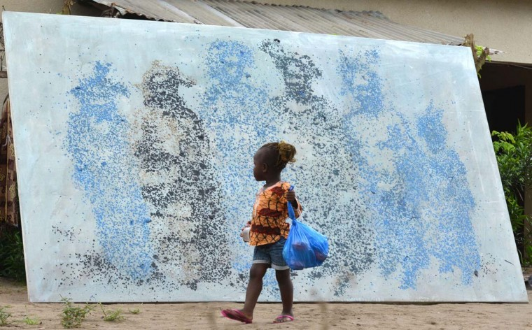 A child walks past a painting by Ivory Coast artist Lanin Saint-Etienne Yeanzi on September 3, 2015 in the Bingerville of Abidjan, made from melted plastic bags.  || CREDIT: ISSOUF SANOGO - AFP/GETTY IMAGES