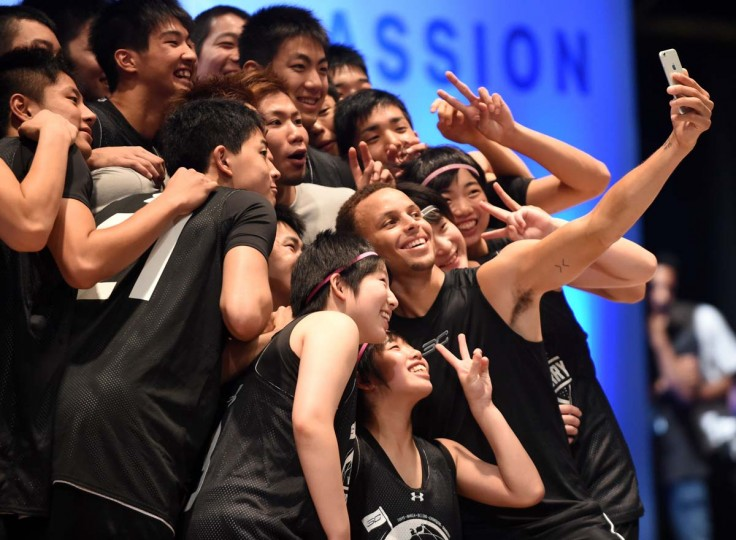"Golden State Warriors 2014-2015 season MVP Stephen Curry takes a selfie with Japan's Under-18 players during a basketball clinic in Tokyo on September 4, 2015. Curry started his three-nation Under Armour Asia tour to promote the company's limited basketball shoes, ""UA Curry II"".   