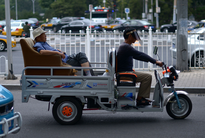 An elderly man sits on a sofa as he is transported on as electric carrier tricycle along a road in Beijing on Tuesday. (WANG ZHAOWANG ZHAO/AFP/Getty Images)