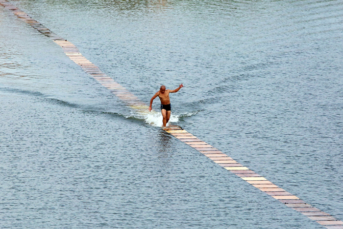 "This picture taken on Aug. 29 shows a Shaolin monk breaking his own world record for ""running on water"" in Quanzhou, Fujian province. Shi Liliang, from the Quanzhou Shaolin Temple, managed to run 125 metres on 200 plywood planks laid across a reservoir, according to local media. It took three attempts before Shi succeeded in breaking his previous record of 120 metres. The task demands excellent balance and great speed, according to reports.  (CHINA OUTSTR/AFP/Getty Images)"