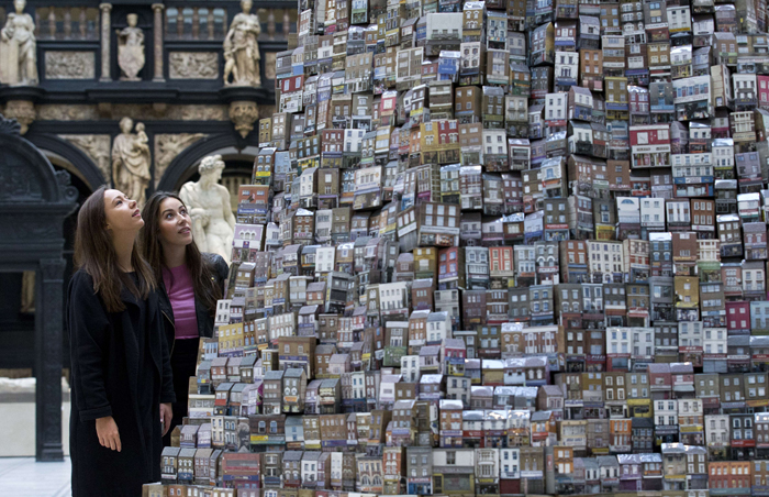 "Visitors pose for pictures beside an artwork titled ""The Tower of Babel"" by British artist Barnaby Barford during a photocall at the Victoria & Albert Museum in London on Tuesday. The 6m high ceramic artwork is composed of 3,000 individual three dimensional bone china buildings, each measuring 10  13cm tall and each depicting a real London shop. The artist photographed over 6,000 shop fronts in the process of making the tower. (JUSTIN TALLIS/AFP/Getty Images)"