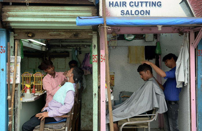 Indian barbers attend to customers at their roadside salons in Mumbai on Tuesday. (INDRANIL MUKHERJEE/AFP/Getty Images)