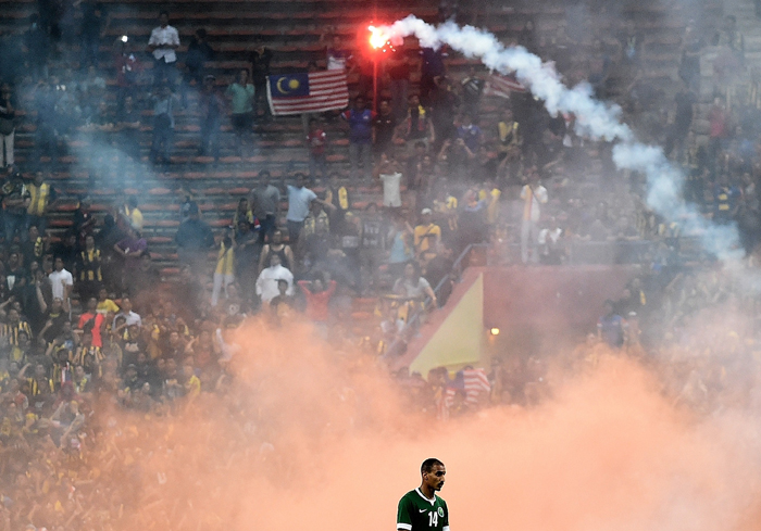 Yasyn Alnakhli of Saudi Arabia walks off the pitch after flares were thrown on the pitch during the 2018 World Cup qualifying football match between Malaysia and Saudi Arabia in Shah Alam on Tuesday. (MANAN VATSYAYANA/AFP/Getty Images)