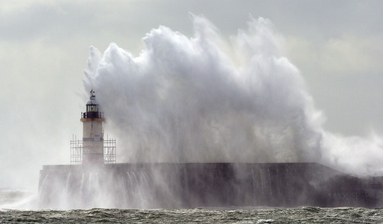 Waves crash into the harbor wall and over the lighthouse at Newhaven on the south coast of England on Monday during high winds. (GLYN KIRK/AFP/Getty Images)
