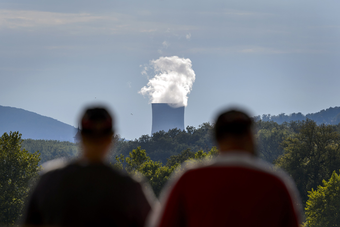 Two men stand facing the cooling tower of the nuclear power plant of Goesgen from the city of Aarau on Saturday. (FABRICE COFFRINI/AFP/Getty Images)