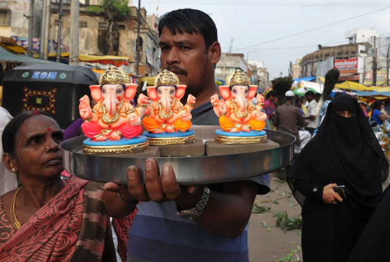 An Indian vendor waits for customers as he sells statuettes of the Hindu god Lord Ganesh ahead of the Ganesh Chaturthi festival at a makeshift market in Hyderabad on September 16, 2015. The popular twelve-day Hindu religious festival 'Ganesh Chaturthi' will be celebrated from September 17-27 this year. (Noah Seelam/AFP/Getty Images)