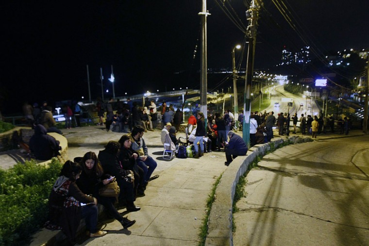 People remain in the street after a tsunami alert in Valparaiso, Chile on September 16, 2015. A strong 7.9-magnitude earthquake struck the center of Chile on Wednesday, US seismologists said, triggering a tsunami alert that stretched to Peru and the evacuation of coastal areas. (AFP Photo/P )