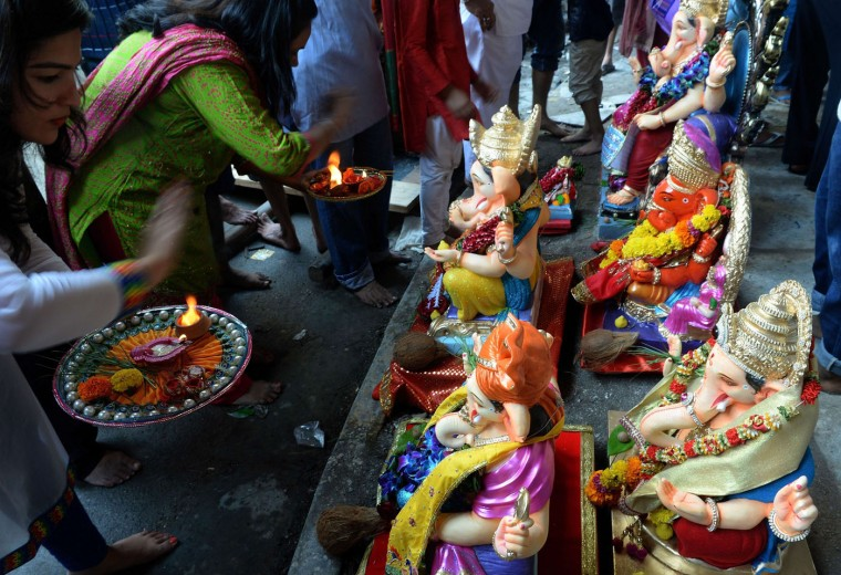 Indian Hindu devotees perform a ritual worship before transporting idols of the elephant-headed Hindu god Lord Ganesha from an artist's workshop for Ganesh Chaturthi in Mumbai on September 17, 2015. The Ganesh Chaturthi festival, a popular 11-day religious festival which is annually celebrated across India, runs this year from September 17-27, and culminates with the immersion of the idols in the Arabian Sea and local water bodies. (Indranil Mukherjee/AFP/Getty Images)