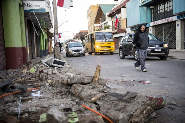 A man crosses a street next to rubble from a collapsed house after an earthquake in Illapel, some 200 km north of Santiago on September 17, 2015. A powerful 8.3-magnitude earthquake struck off Chile on September 17, killing eight people, forcing the evacuation of a million and sparking warnings that tsunami waves could reach Japan. (AFP Photo/P )