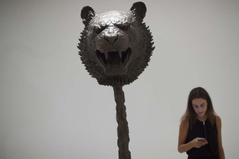 """A woman checks her smartphone past a sculpture titled """"Circle of Animals / Zodiac Heads and representing a bear head of Chinese artist Ai Weiwei at the Contemporary Art Centre """"CAC"""" in Malaga on September 18, 2015. The exhibition will be open from September 18 to December 6, 2015.    