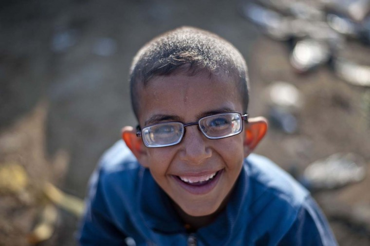 A Syrian boy smiles after crossing the Greek-Macedonian border near Gevgelija on September 18, 2015. Land routes to northern Europe from the Balkans were all closed for migrants, after Croatia closed their border with Serbia because of the unprecedented human wave.  The crisis, challenging the EU's humanitarian reputation and its vaunted policy of border mobility, has triggered an extraordinary summit, bringing leaders of the 28-nation bloc together next week.  || CREDIT: NIKOLAY DOYCHINOV - AFP/GETTY IMAGES