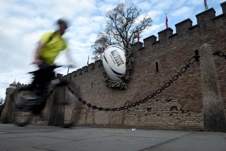 A man cycles past a giant rugby ball breaking the wall of Cardiff castle on September 18, 2015, ahead of the 2015 Rugby Union World Cup.  || CREDIT: DAMIEN MEYER - AFP/GETTY IMAGES