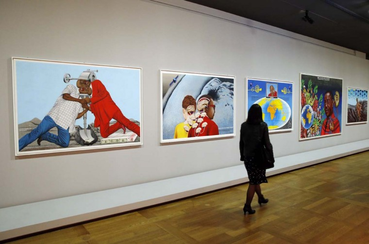 A visitor walks past pictures by artist Cheri Samba from the Democratic Republic of Congo that are part of the exhibition 'A Brief History of the Future' (Une brève histoire de l'avenir) during a press preview at the Louvre museum in Paris on September 18, 2015. The exhibition will be open to the public from September 24, 2015 until January 4, 2016.  || CREDIT: PATRICK KOVARIK - AFP/GETTY IMAGES