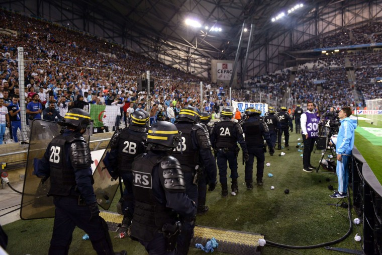 Riot police are pictured during a game interruption after crowd trouble during the French L1 football match Marseille (OM) vs Lyon (OL) on September 20, 2015 at Velodrome Stadium in Marseille, southern France. The match restarted after a 20-minute delay. (AFP Photo/Franck Pennant)