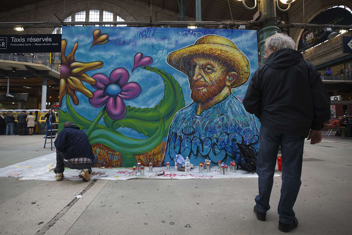 A man stops to observe as French artist Nowart puts the final touches on a mural in tribute to Dutch painter Vincent Van Gogh at the Gare du Nord train station in Paris on Tuesday. (JOEL SAGET/AFP/Getty Images)