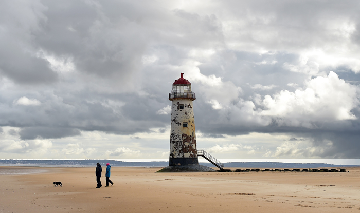 People walk with a dog as they cross the beach near the Point of Ayr Lighthouse in Talacre in north Wales on Tuesday. A lighthouse has stood on the site since 1776, but the current one was discontinued in 1883 after being replaced by a lightship, situated off of the north Wales coast. The lighthouse is the oldest in Wales. (PAUL ELLIS/AFP/Getty Images)